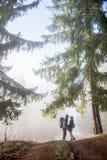 Randonneurs d'homme et de femme appréciant sur la traînée de montagne brumeuse de forêt Images stock