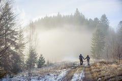 Randonneurs d'homme et de femme appréciant sur la traînée de montagne brumeuse de forêt Photos libres de droits