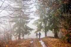 Randonneurs d'homme et de femme trimardant sur la traînée de montagne brumeuse de forêt Image stock