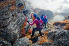Randonneurs de couples avec des sacs à dos dans les montagnes Image stock