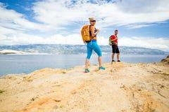Randonneurs de couples marchant sur la traînée au bord de la mer Images stock