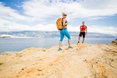 Randonneurs de couples marchant sur la traînée au bord de la mer Photographie stock libre de droits