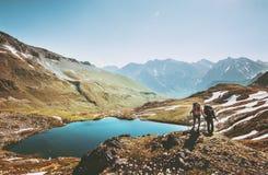 Randonneurs de couples trimardant en montagnes au-dessus de lac Image libre de droits