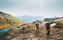 Randonneurs de couples trimardant ensemble en montagnes Image stock