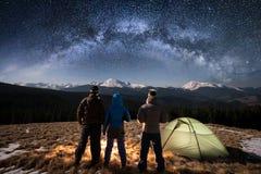 Randonneurs de couples de vue arrière tenant les mains et leur ami sous le beau ciel nocturne plein des étoiles et de la manière  Image stock