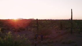 Randonneurs de désert au coucher du soleil avec des fusées de lentille clips vidéos