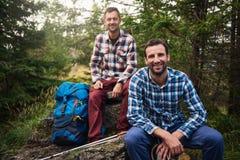 Randonneurs de sourire faisant une pause dans les bois Photographie stock libre de droits