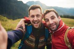 Randonneurs de sourire prenant un selfie ensemble dans la région sauvage Image stock