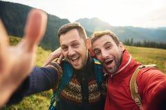 Randonneurs de sourire prenant un selfie tandis que trekking dans la région sauvage Image libre de droits