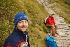 Randonneurs de sourire se reposant sur une traînée de montagne rocailleuse Photographie stock libre de droits