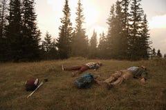 Randonneurs fatigués se trouvant sur l'herbe après un voyage Photographie stock