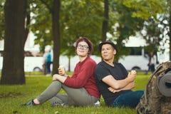 Randonneurs heureux de couples mangeant la crème glacée se reposant sur l'herbe Images libres de droits