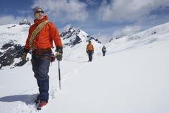 Randonneurs jointifs par la ligne de sécurité sur des montagnes de Milou Photographie stock libre de droits