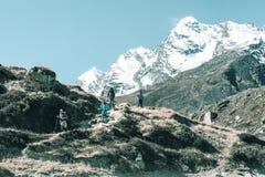 Randonneurs marchant sur le sentier piéton dans les montagnes et le désert peu communs de terrain photographie stock libre de droits