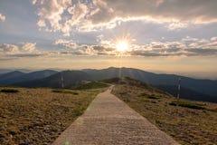 Randonneurs marchant sur une montagne au coucher du soleil Image stock