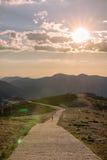 Randonneurs marchant sur une montagne au coucher du soleil Photo libre de droits