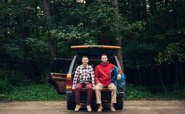 Randonneurs s'asseyant sur une voiture prête à aller trekking de région sauvage Photo stock