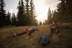 Randonneurs se reposant sur l'herbe après un long voyage de région sauvage Photos libres de droits