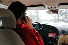 Driver uses a cell phone. Ranea, Sweden - March 29, 2014: The driver uses a handheld mobile phone while driving the car royalty free stock photography