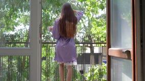 Ranek, dama w koszula nocnej iść balkon hotel z podwyżki ręką na świeżym powietrzu i filiżanką zbiory