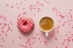 Ranek filiżanka i cukierki ciasto różowy jagodowy pączek i serce kształtujący kropimy na różowym pastelowym stołowym odgórnym wid zdjęcia stock
