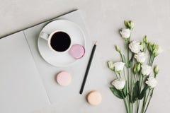 Ranek filiżanka kawy, pusty notatnik, ołówek, biali kwiaty i tortowy macaron na szarość stole od above, piękny śniadanie Fotografia Stock