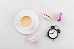 Ranek filiżanka kawy, tortowy macaron i budzik na lekkim stołowym odgórnym widoku w mieszkanie nieatutowym stylu, piękny śniadani Fotografia Royalty Free