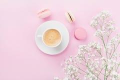 Ranek filiżanka kawy, tortowy macaron i kwiaty na różowym stołowym odgórnym widoku w mieszkaniu, kłaść styl Piękny śniadanie dla  Obrazy Stock