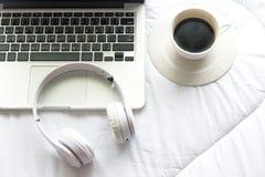 Ranek muzyki tło Kawa z laptopem w białym łóżku, prześcieradle, duvet i poduszce bałaganiących up, Zdjęcia Royalty Free