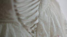 Ranek panna młoda gosposia pomaga panny młodej z jej suknią honor panny młodej ` s zasznurowywa up suknię Drużka wiąże łęk dalej zdjęcie wideo