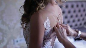 Ranek panna młoda gosposia pomaga panny młodej z jej suknią honor panny młodej ` s zasznurowywa up suknię Drużka wiąże łęk dalej zbiory wideo