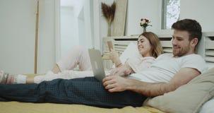 Ranek rutyna dla pary w łóżku, kobieta czyta książkę i jej partner, jesteśmy przyglądający na laptopie Strzelający na Czerwonej e zdjęcie wideo