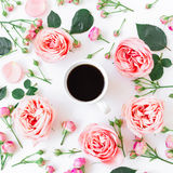 Ranek tło Kwiecista rama z menchiami kwitnie, pączki, liście i kawowy kubek na białym tle, Mieszkanie nieatutowy, odgórny widok Zdjęcie Royalty Free