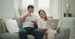 Ranek wpólnie dla jeden pary wydaje czas wpólnie na kanapa mężczyźnie pije kawowego damy dopatrywanie w piżamach zbiory
