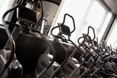 Rangée d'entraîneur croisé elliptique dans le club de sport moderne de fitnes Photos libres de droits
