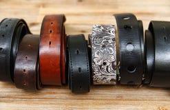 Rangée de beaucoup de ceintures en cuir plan rapproché Fond en bois Image libre de droits