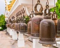Rangée de Bells en bronze superficielles par les agents dans le temple de bouddhisme, Thaïlande Photo libre de droits
