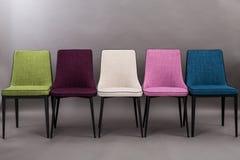 Rangée de cinq chaises dinning modernes d'isolement sur le fond gris Série de meubles Photo stock