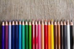 Rangée de crayon de couleur sur le fond en bois photos stock