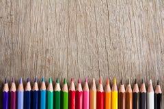 Rangée de crayon de couleur sur le fond en bois images stock