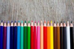 Rangée de crayon de couleur sur le fond en bois image stock
