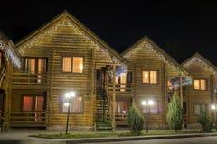 Rangée de nouveaux hôtels décorés confortables en bois écologiques deux-racontés de cottages sur la rue lumineuse propre sous le  images libres de droits