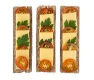 Rangée de pain croquant avec du fromage, des concombres et des tomates image libre de droits
