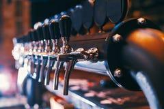Rangée de robinet de bière dans la barre de bière image stock