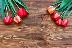 Rangée de sept tulipes sur le fond en bois avec l'espace pour votre message Photographie stock
