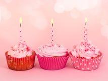 Rangée de trois petits gâteaux avec des bougies Images stock