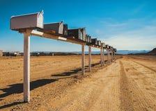 Rangée de vieilles et superficielles par les agents boîtes aux lettres dans le désert Images stock
