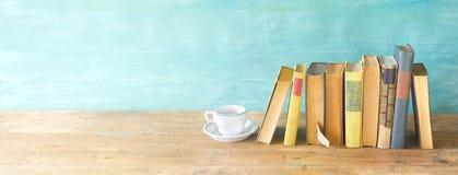 Rangée de vieux livres et d'une tasse de café sur des étagères à livres rustiques Photos stock