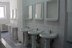 Rangée des éviers et des miroirs dans une nouvelle toilette publique image stock
