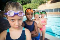 Rangée des amis se tenant sur le côté de piscine Image libre de droits